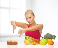 Woman with fruits showing thumbs down to cake Stock Image
