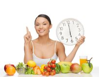 Woman with fruits, vegetables and clock Stock Photos
