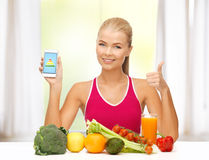Woman with fruits, vegetables and smartphone. Sporty woman with fruits and vegetables showing smartphone Royalty Free Stock Photo