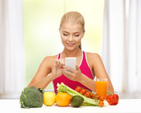 Woman with fruits, vegetables and smartphone. Woman with fruits and vegetables counting calories on smartphone Royalty Free Stock Photos