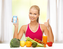 Woman with fruits, vegetables and smartphone. Sporty woman with fruits and vegetables showing smartphone Stock Image