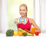Woman with fruits, vegetables and smartphone. Woman with fruits and vegetables counting calories on smartphone Stock Images