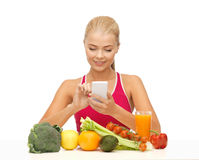 Woman with fruits, vegetables and smartphone. Woman with fruits and vegetables counting calories on smartphone Stock Photos