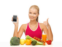 Woman with fruits, vegetables and smartphone. Sporty woman with fruits and vegetables showing smartphone Royalty Free Stock Photos