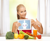 Woman with fruits, vegetables and tablet pc. Sporty woman with fruits and vegetables pointing at tablet pc Stock Photos
