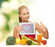 Woman with fruits, vegetables and tablet pc. Fitness, diet, technology, health and food concept - sporty woman with fruits and vegetables pointing at tablet pc Royalty Free Stock Photography