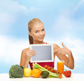 Woman with fruits, vegetables and tablet pc. Fitness, diet, technology, health and food concept - sporty woman with fruits and vegetables pointing at tablet pc Royalty Free Stock Image