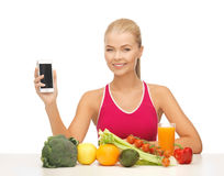 Woman with fruits, vegetables and tablet pc. Woman with fruits and vegetables counting calories in smartphone Stock Photo