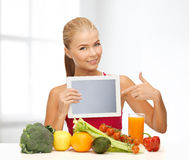 Woman with fruits, vegetables and tablet pc. Fitness, diet, technology, health and food concept - sporty woman with fruits and vegetables pointing at tablet pc Stock Photography
