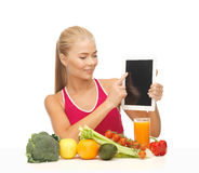 Woman with fruits, vegetables and tablet pc. Sporty woman with fruits and vegetables pointing at tablet pc Royalty Free Stock Photography
