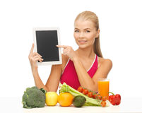 Woman with fruits, vegetables and tablet pc. Sporty woman with fruits and vegetables pointing at tablet pc Stock Images