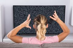 Woman Frustrated With A TV Screen Glitch royalty free stock photos