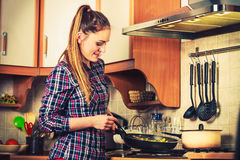 Woman frying frozen vegetables. Stir fry. Royalty Free Stock Images