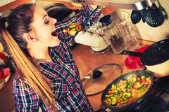 Woman frying frozen vegetables. Stir fry. Woman in kitchen cooking stir fry frozen vegetables and tasting. Girl frying making delicious dinner food meal royalty free stock image