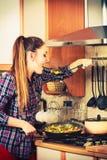Woman frying frozen vegetables. Stir fry. Stock Photography