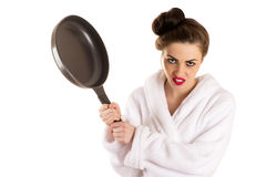 Woman with a frying pan in a hand in white bathrobe Royalty Free Stock Image
