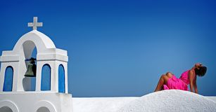 woman in fuchsia dress on blue sky background of Santorini, Oia stock image