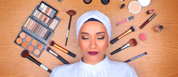 Woman in full makeup surrounded by makeup stock image