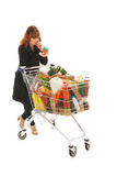 Woman with full shopping cart reading label. Critical costumer reading label from groceries in supermarket Stock Image