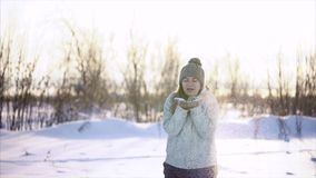 Woman fun with the snow on a winter day. She blows snow that lies on her hands. stock video footage