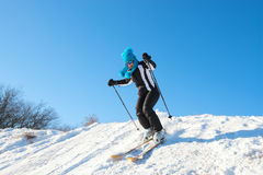 Woman in funny cap skiing on background of blue sky Stock Photos