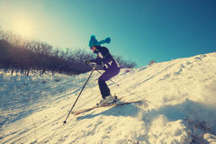 Woman in funny cap skiing downhill in winter forest Royalty Free Stock Photos