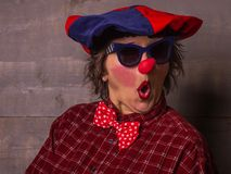 Woman funny clown with red nose and blue sunglasses. Comedy conc. Comedian clown with a  blue-red big beret, big red nose and blue sunglasses Royalty Free Stock Images