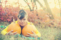 Woman with funny face is resting near with big pumpkins Stock Images