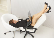 Woman funny located in office chairs with laptop Stock Photo