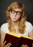 Woman in funny old-fashioned glasses reading book Stock Photo