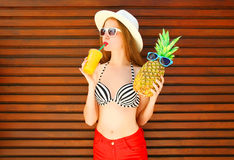 Woman with funny pineapple drinks juice or smoothies. On wooden background stock photography