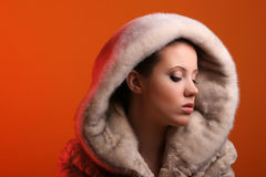 Woman in fur. Attractive woman wearing fur isolated on orange background Royalty Free Stock Photography
