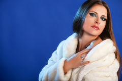 Woman in fur on blue background winter style diamond ring and lu Royalty Free Stock Images