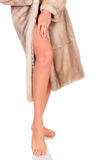 Woman in fur coat. Showing her well-groomed legs, white background Royalty Free Stock Images