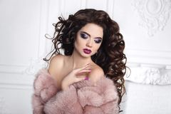 Woman in fur coat. Curly hair. Beautiful Brunette Girl portrait. Manicured nails. Beauty glitter eyeshadows makeup. Long healthy Hairstyle. Fashion brunette Stock Photography