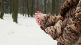woman in fur coat.Girls is trying to warm up freezing hands. stock footage
