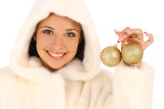 Woman in fur coat with gold christmas balls. Young beautiful woman in fur coat with gold christmas balls on white background Stock Photography