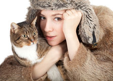 Woman in a fur coat and hat with cat Stock Images