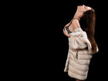 Woman in fur coat. Luxury woman in fur coat showing big breast on black background with copyspace Stock Photography