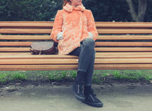 Woman in fur coat sitting on bench Royalty Free Stock Photo