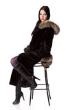 Woman in fur-coat is sitting on a chair Royalty Free Stock Image