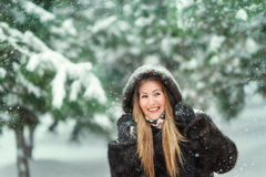 Woman in a fur coat in snowy woods Stock Photos