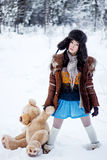 Woman in fur coat and ushanka with bear on white snow winter background Stock Photo
