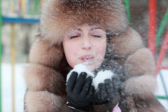 Woman in fur hat blowing snowflakes in winter. Beautiful young woman in fur hat blowing snowflakes in winter, children's playground Royalty Free Stock Image