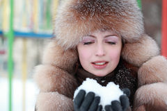 Woman in fur hat keeps snow in winter. Beautiful young woman in fur hat keeps snow in winter, children's playground Royalty Free Stock Photography