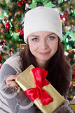 Woman in fur hat and mitten holding Christmas present Stock Images