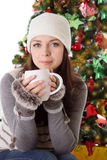 Woman in fur hat and mittens with mug. Under Christmas tree Royalty Free Stock Images