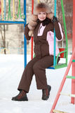 Woman in fur hat sits on swing in winter Stock Photography