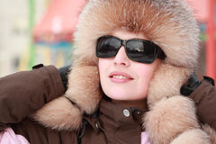 Woman in fur hat and sunglasses in winter. Beautiful young woman in fur hat and sunglasses in winter, children's playground Stock Image
