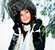 Woman with fur hat in Winter. Half body portrait of happy young woman with large fur hat in snow covered Wintry forest Stock Photo